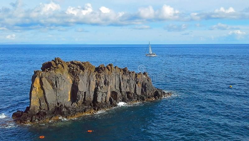 Beautiful sailboat on the background rocks in the atlantic ocean royalty free stock photo