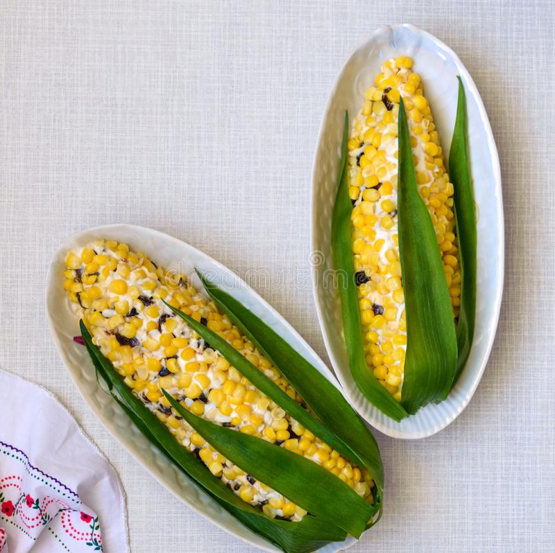 Beautiful salad in the form of corn for the holiday table. Salad of corn, prunes, cheese, eggs in plates stock photo