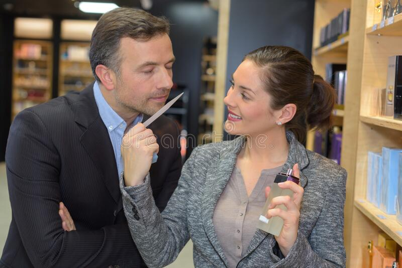 Beautiful saleswoman showing beauty products to male customer royalty free stock image