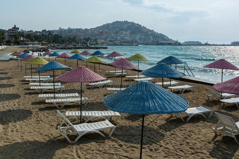 Beautiful sand beach of Kusadasi with colorful straw umbrellas and lounge chairs, Aegean Sea,Turkey. stock images