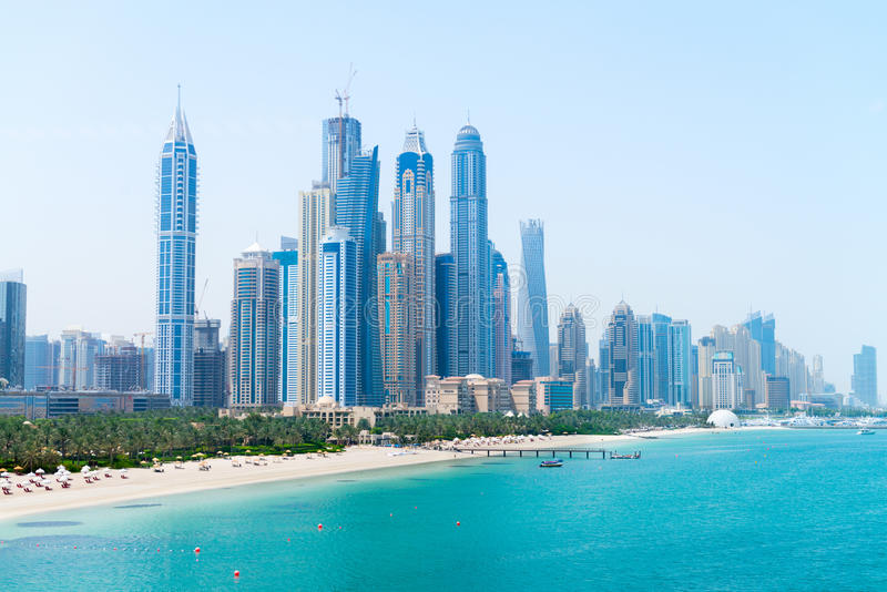 Beautiful Sandy Beach and Modern Metropolitan Skyline. Tall skyscrapers of a modern, metropolitan cityscape tower over a beautiful, white, sandy beach on a warm royalty free stock images