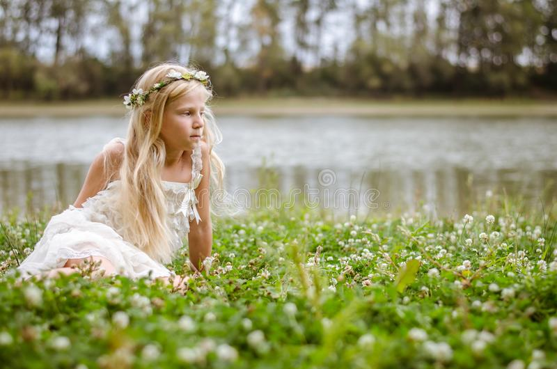 Little lovely girl sitting in the grass by the river royalty free stock photos