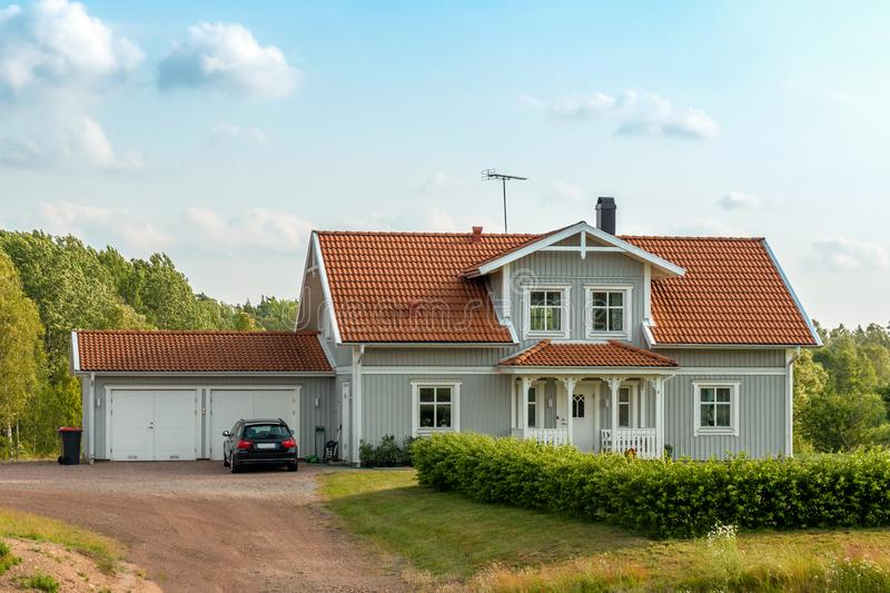 Beautiful scandinavian style house with two places garage and gar in fron of it. Summer with blue scky and green grass. In front of house, architecture stock photography