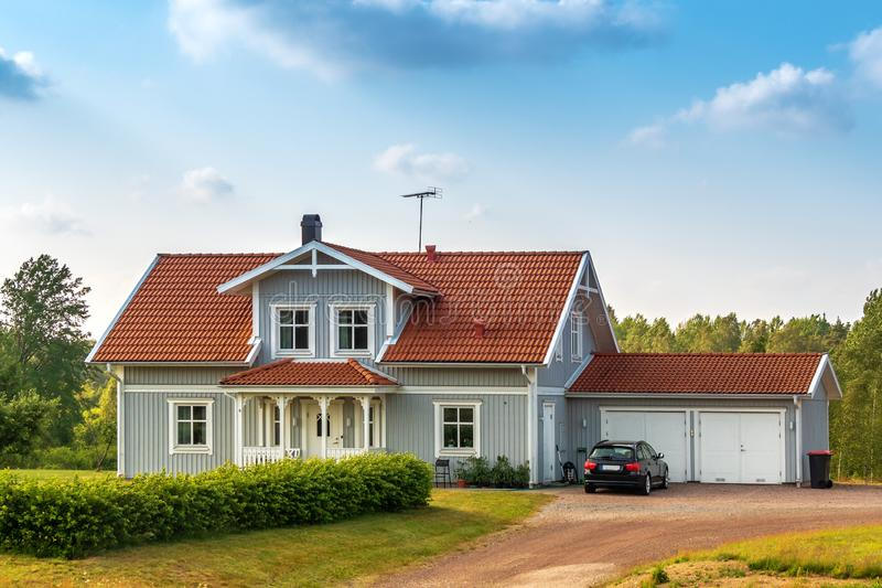 Beautiful scandinavian style house with two places garage and gar in fron of it. Summer with blue scky and green grass. In front of house, architecture stock photo