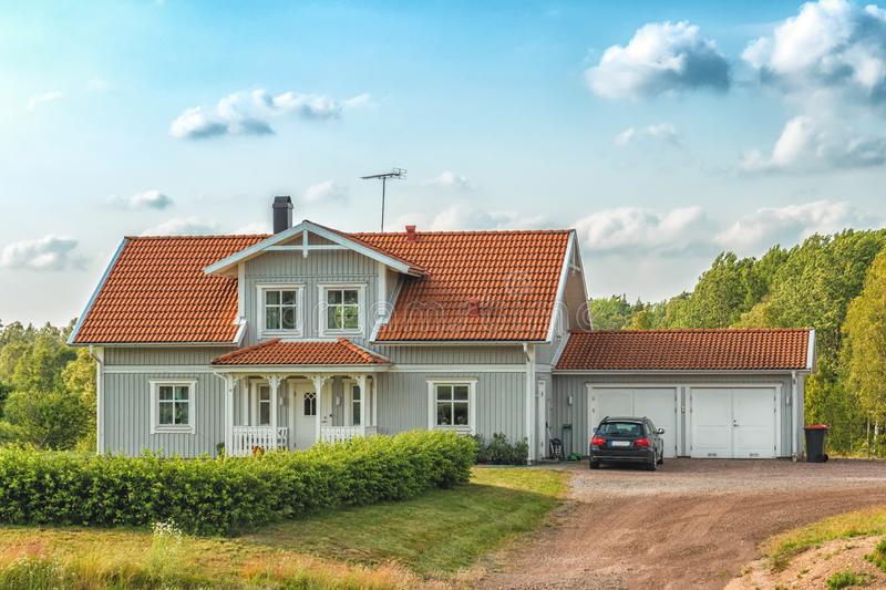 Beautiful scandinavian style house with two places garage and gar in fron of it. Summer with blue scky and green grass. In front of house, architecture royalty free stock images