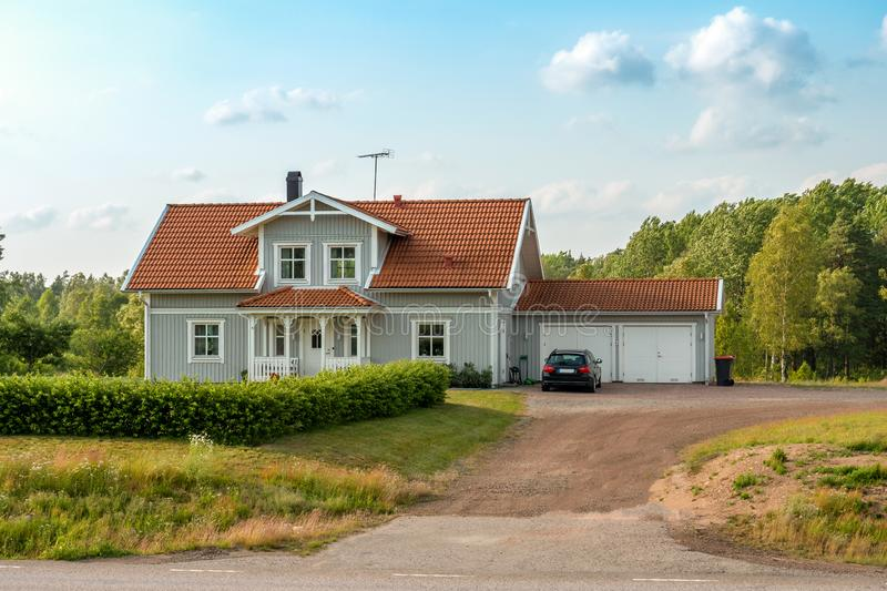 Beautiful scandinavian style house with two places garage and gar in fron of it. Summer with blue scky and green grass. In front of house, architecture stock images