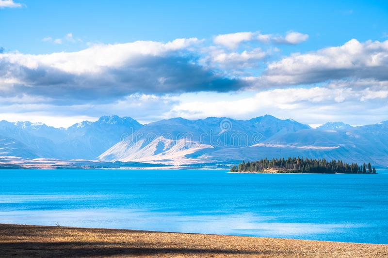 Beautiful scene of blue lake and yellow grassland with mount cook beside lake Tekapo before sunset. I. Beautiful scene of blue lake and yellow grassland with royalty free stock photos