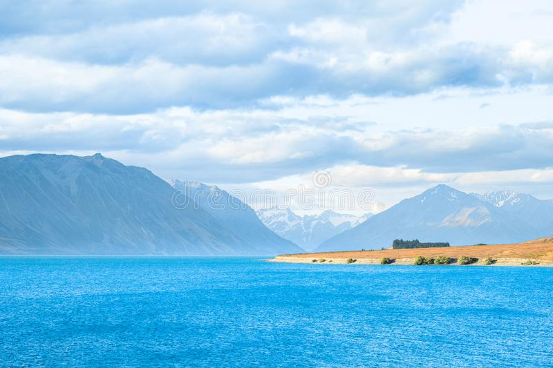 Beautiful scene of blue lake and yellow grassland with mount cook beside lake Tekapo before sunset. I. Beautiful scene of blue lake and yellow grassland with stock photography