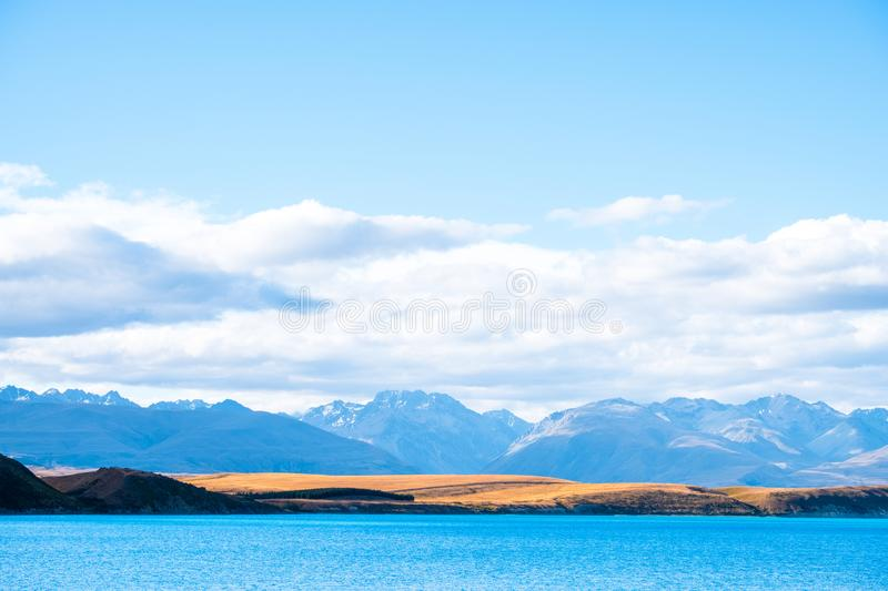 Beautiful scene of blue lake and yellow grassland with mount cook beside lake Tekapo before sunset. I. Beautiful scene of blue lake and yellow grassland with royalty free stock image