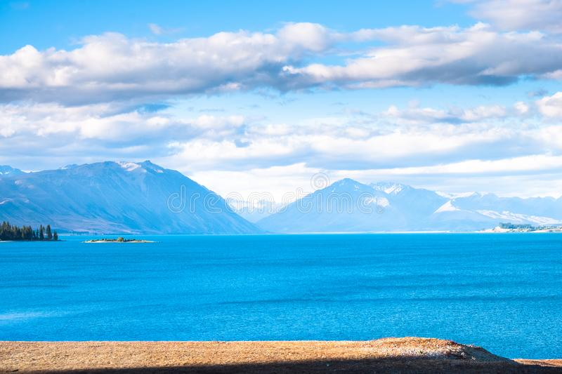 Beautiful scene of blue lake and yellow grassland with mount cook beside lake Tekapo before sunset. I. Beautiful scene of blue lake and yellow grassland with royalty free stock photography