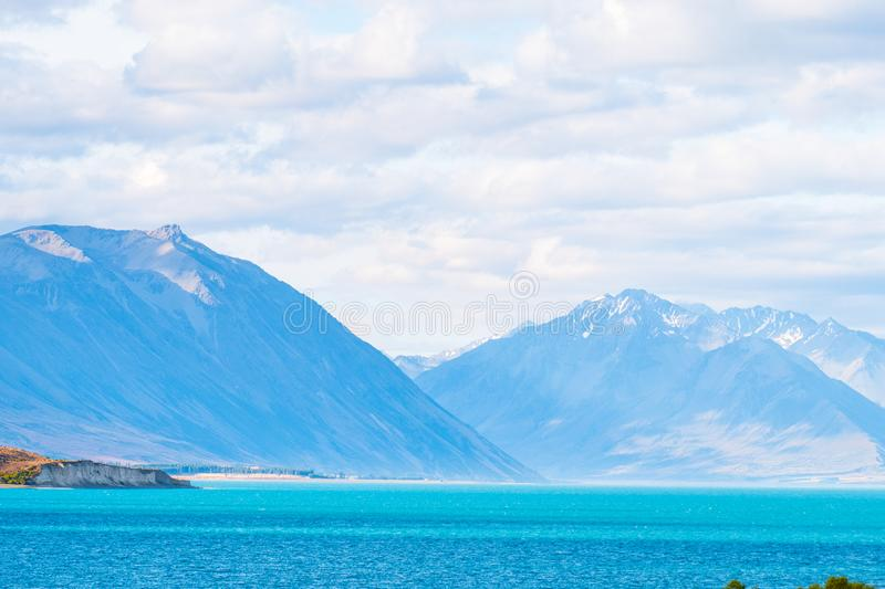 Beautiful scene of blue lake and yellow grassland with mount cook beside lake Tekapo before sunset. I. Beautiful scene of blue lake and yellow grassland with stock images