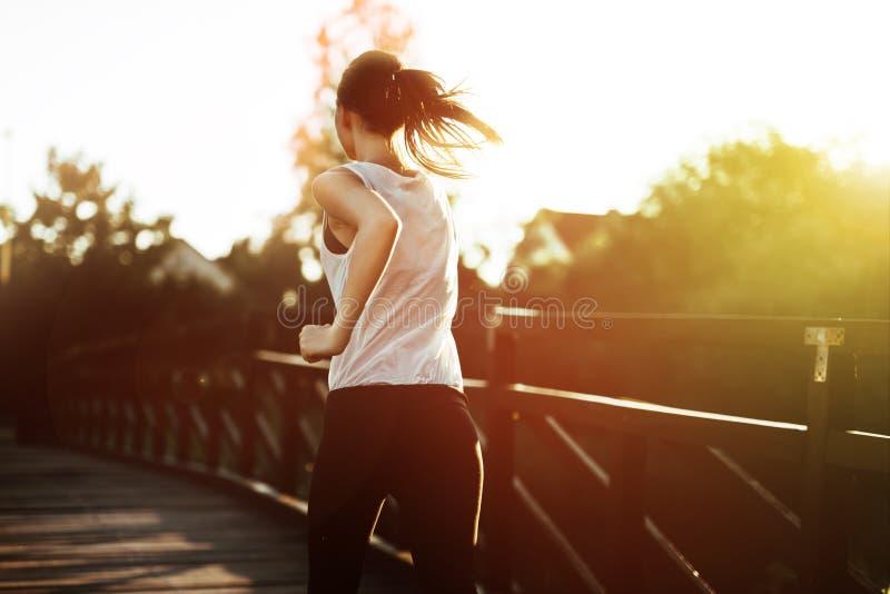 Beautiful scene of female jogger. Crossing bridge stock image