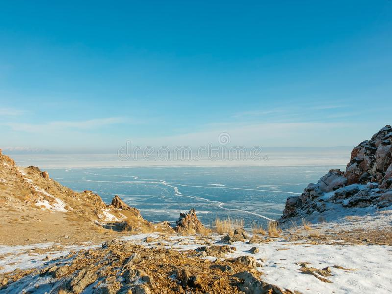 Landscape of frozen Lake Baikal in winter with background of hills and blue sky from view point cape at Olkhon island. Beautiful scene of frozen Lake Baikal royalty free stock image