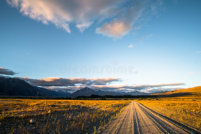 Beautiful scene of the road among the yellow grassland and the mountain beside lake Tekapo. I. Beautiful scene of the road among the yellow grassland and the royalty free stock photography
