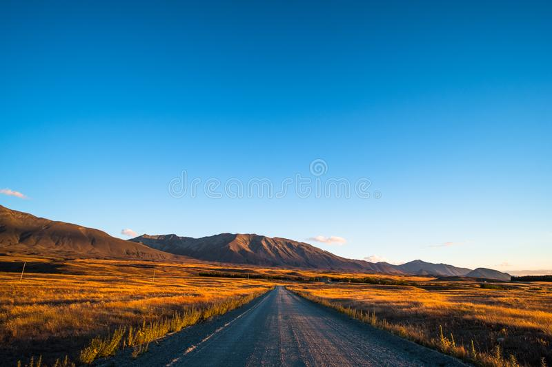 Beautiful scene of the road among the yellow grassland and the mountain beside lake Tekapo. I. Beautiful scene of the road among the yellow grassland and the stock image