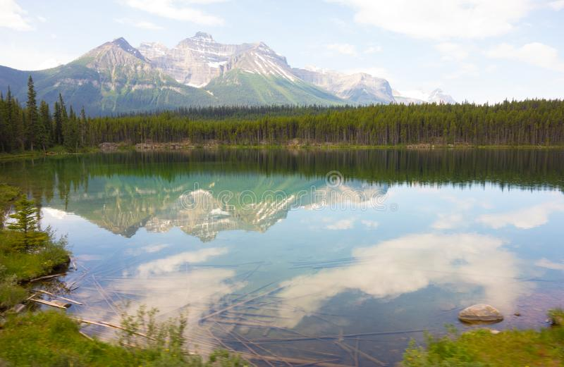 Mountains reflected in a calm lake in the rockies. A beautiful scene of the rockies in the summertime stock photo