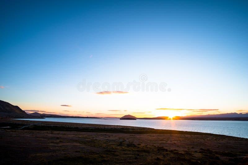 Beautiful scene of the sunset over the lake with yellow grassland at lake tekapo. I. Beautiful scene of the sunset over the lake with yellow grassland at lake royalty free stock photo