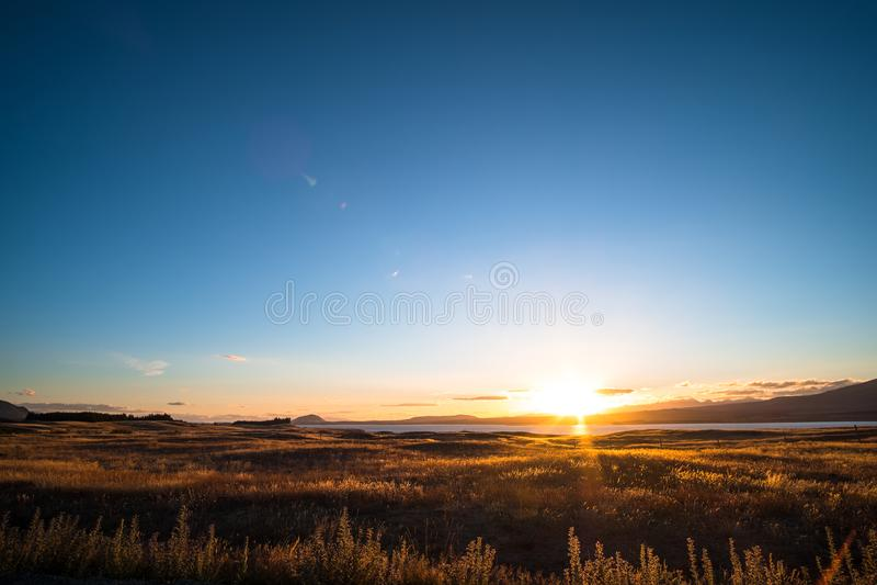 Beautiful scene of the sunset over the lake with yellow grassland at lake tekapo. I. Beautiful scene of the sunset over the lake with yellow grassland at lake stock image
