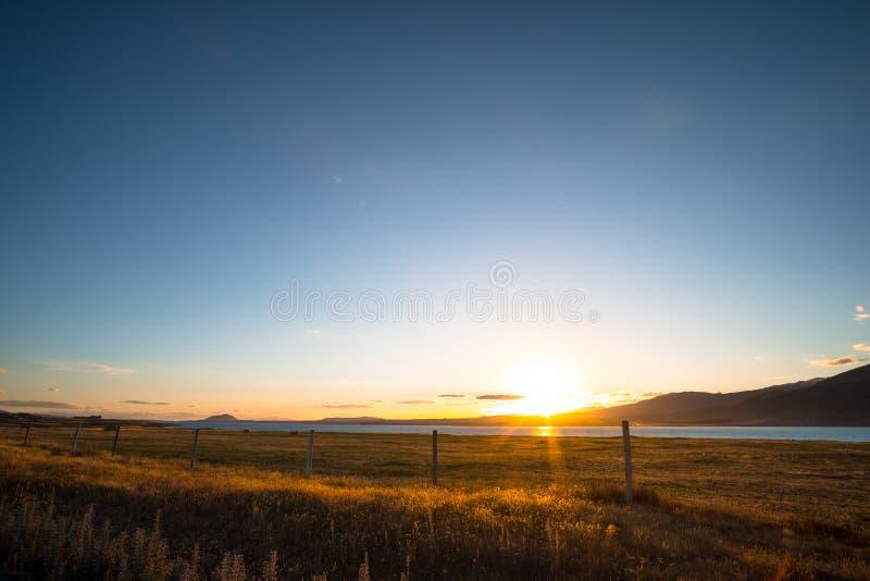Beautiful scene of the sunset over the lake with yellow grassland at lake tekapo. I. Beautiful scene of the sunset over the lake with yellow grassland at lake royalty free stock images