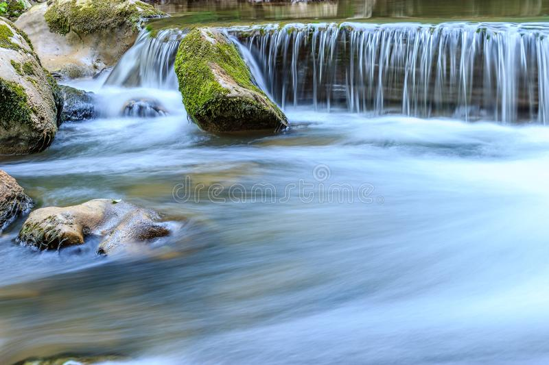 Beautiful scene of waterfall with stone cascade and mossy rocks stock photos
