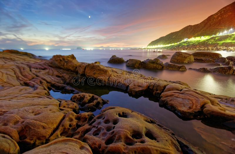 Beautiful scenery of dawning sky by rocky beach in northern Taiwan. With reflection of golden sun light on tranquil sea water ! Romantic view of sunrise by sea stock image