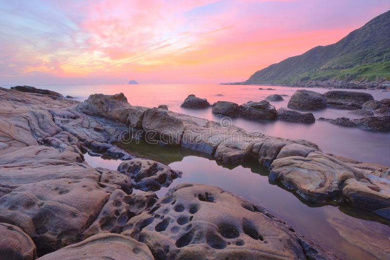 Beautiful scenery of dawning sky by rocky seashore in northern Taiwan (long exposure effect). With beautiful and tranquil reflection of water ~ Wanli District stock photography