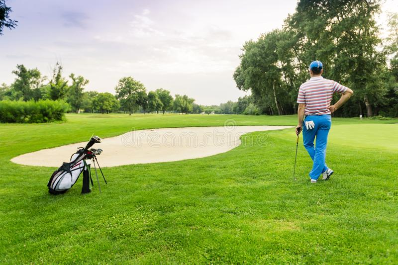 Beautiful golfing scenery with a golfer holding a club royalty free stock photos