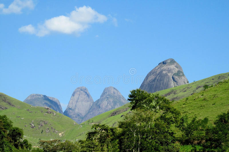 Beautiful scenery of green forest and smooth rocks. Tres Picos, three peaks isolate mountain ofSerra dos Orgaos National Park great stone wall to climb royalty free stock photography