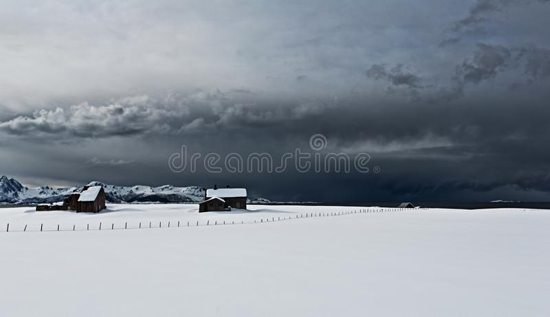 Beautiful scenery of houses in a field covered in snow in Lofoten, Norway. A beautiful scenery of houses in a field covered in snow in Lofoten, Norway stock photography