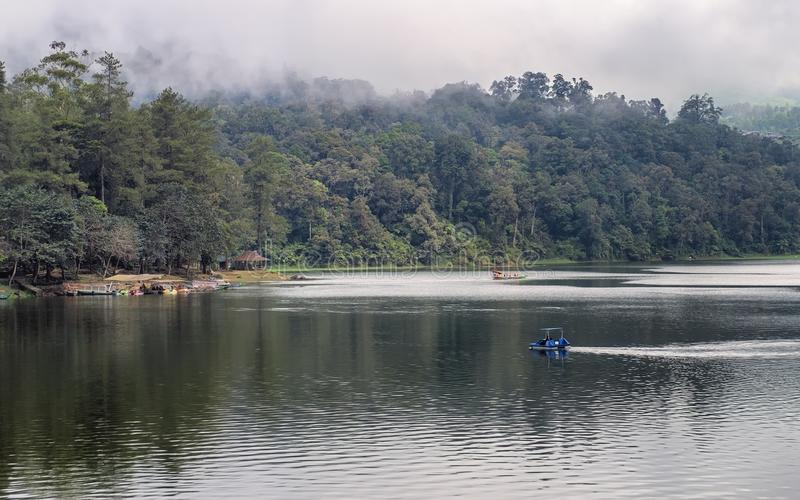 Beautiful scenery of huge lake, with trees, houses and mist create calming atmosphere. In the middle of the lake, there also a little boat exploring the lake stock photos