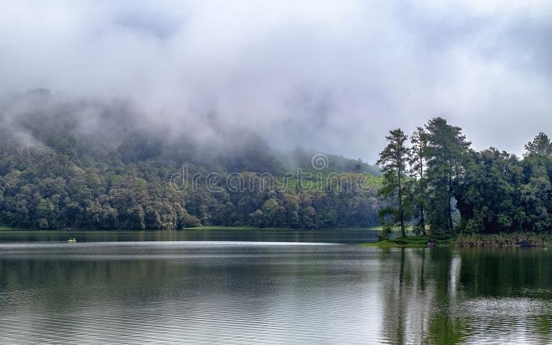 Beautiful scenery of huge lake, with trees, and mist create calming atmosphere. In the middle of the lake, there also a little boat exploring the lake royalty free stock photos