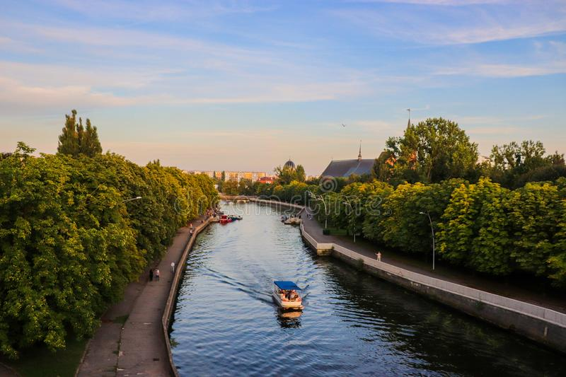 Blue river and a boat in Kaliningrad, Russia. Beautiful city view in European travel destination. stock image