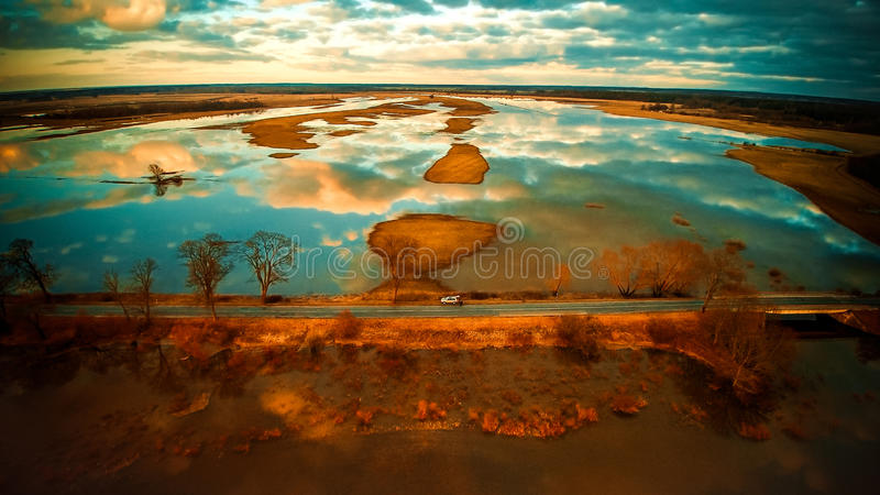 Beautiful scenery. Road at soft orange sunset time, clouds reflected in water stock photos
