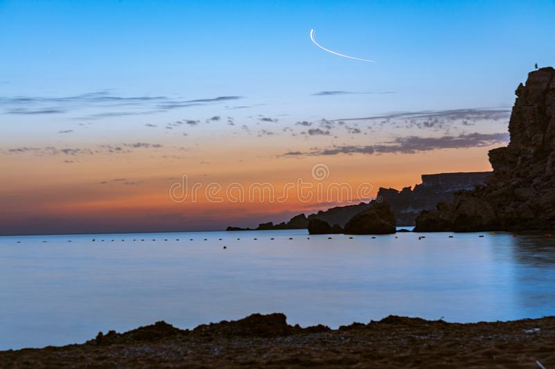 Beautiful scenery of rocky cliffs near the calm sea under the colorful sky during sunset. A beautiful scenery of rocky cliffs near the calm sea under the royalty free stock images