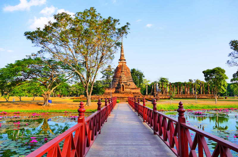 Beautiful Scenery Scenic View A Red Bridge Crossing Traphang-Trakuan Lake to The Ancient Buddhist Temple Ruins of Wat Sa Si in The stock photo