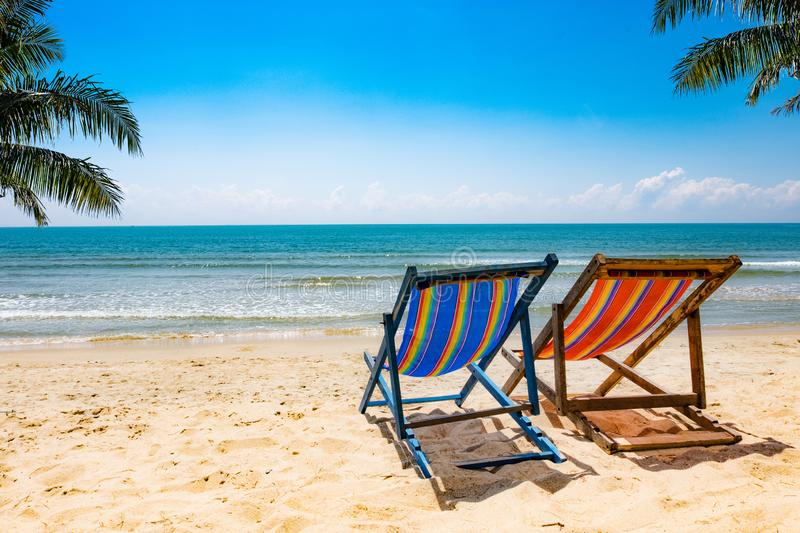 Beautiful scenery of two chairs and a white umbrella on the beach in summer. Copy area banner royalty free stock image