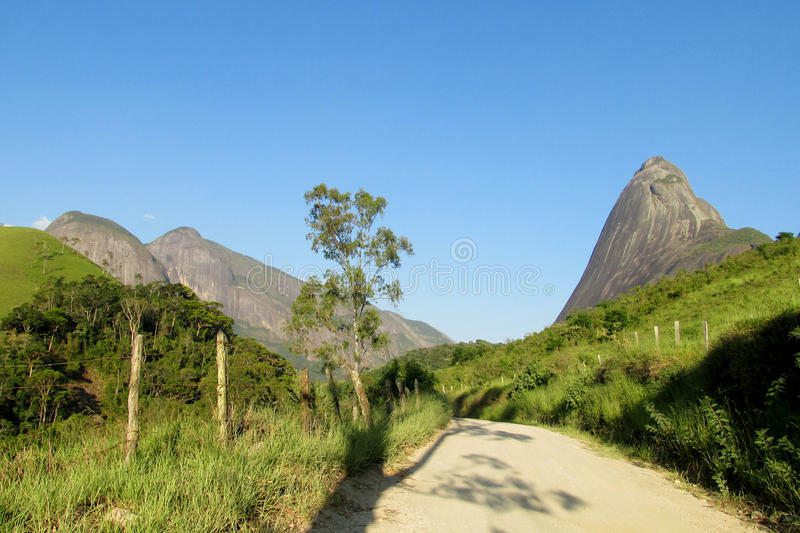 Beautiful scenery of village road and smooth rock. Beautiful scenery of green forest and smooth rocks. Tres Picos, three peaks isolate mountain ofSerra dos royalty free stock photo