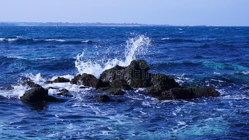 It is a beautiful scenery where a wave crashes against a blue sea rock of Udo, Jeju Island. stock photo