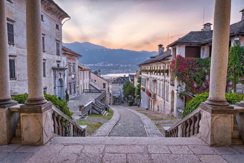 Beautiful scenic alley with historic and traditional houses and cobbled street at sunset. Picturesque Italian village, lake Orta royalty free stock images