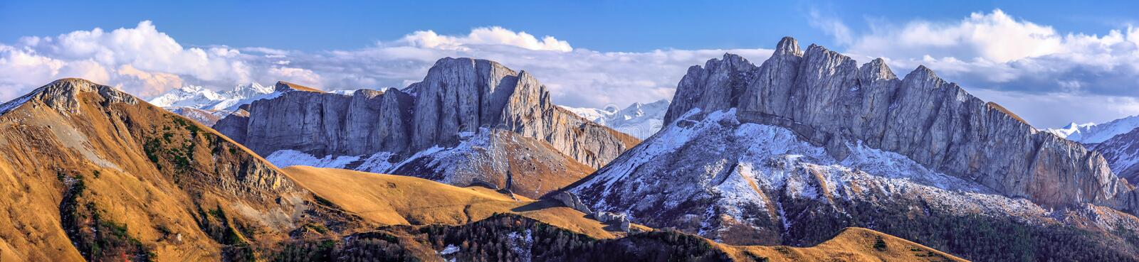 Beautiful scenic autumn landscape of majestic Acheshbok rocky mountain peaks called Devil`s Gate covered with snow under blue sky stock images