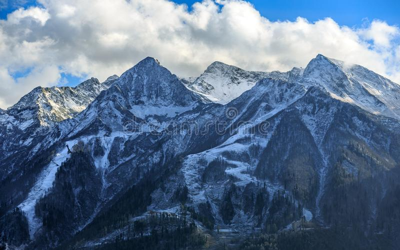 Beautiful scenic autumn landscape of snowy Aibga peaks under blue sky with clouds in Caucasus mountains, ski slopes of Gorky Gorod. Resort, Krasnaya Polyana stock images