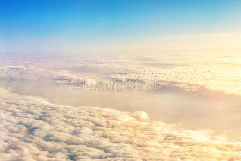 Beautiful scenic dramatic morning sunrise cloudscape aerial view from plane window. Gradient colored fluffy clouds during aircraft royalty free stock photo