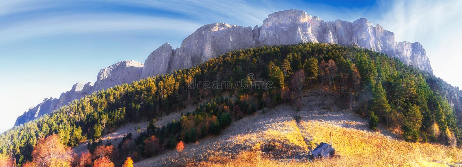 Beautiful scenic golden autumn landscape of majestic Bolshoy Tkhach rocky mountain peak under blue sky at sunrise with wooden tour royalty free stock photos