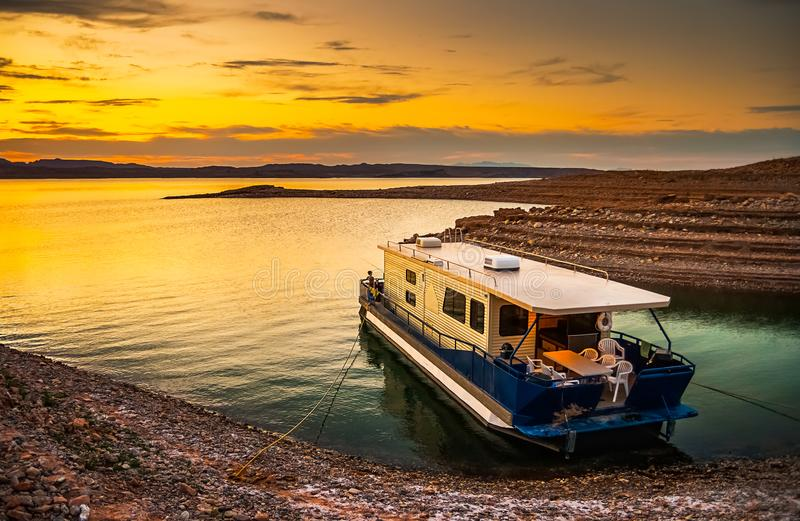 Beautiful and scenic landscape of the Lake Mead. National Recreation Area with a houseboat moored to the shores of a bay with a dramatic sky at sunset, Nevada royalty free stock image