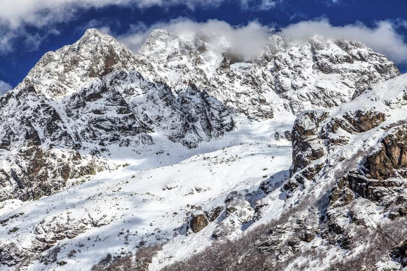 Beautiful scenic landscape of rocky snow covered mountain peaks of Caucasus mountains on sunny day with blue sky and clouds stock image