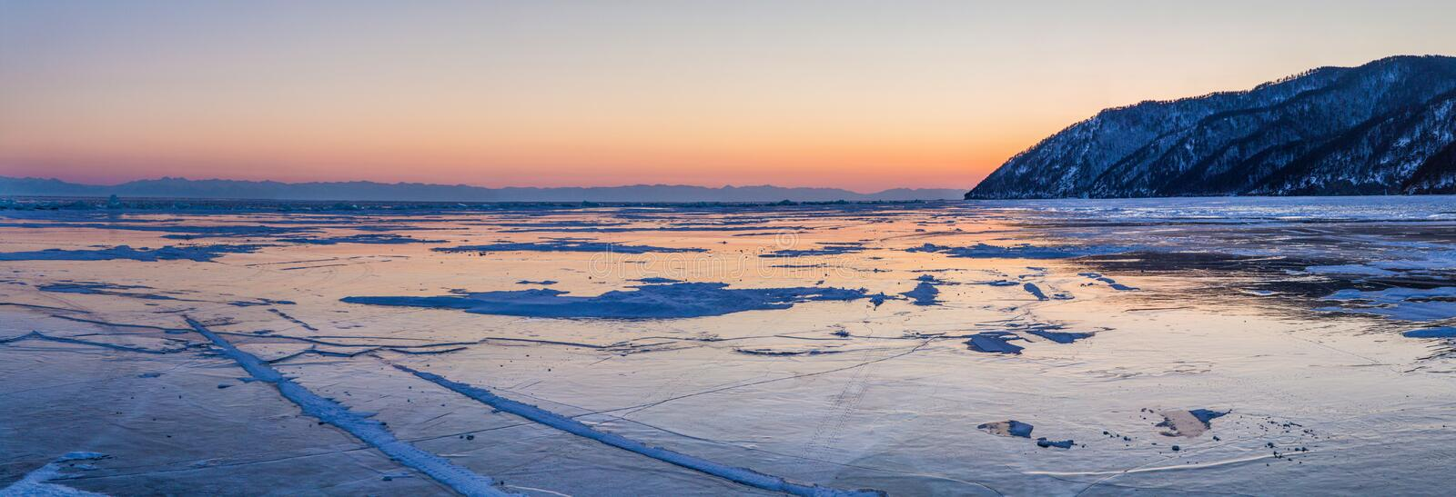 Beautiful scenic landscape with shore and frozen lake Baikal. At sunset royalty free stock photo