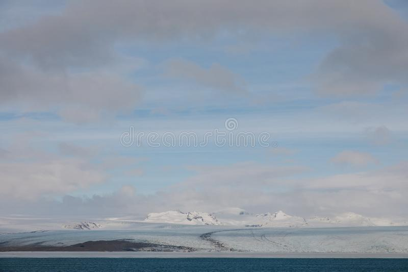 Beautiful scenic landscape with snow-covered hills, water and cloudy sky, iceland,. Jokulsarlon Glacier royalty free stock photo