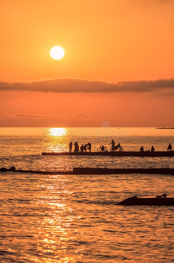Scenic sunset landscape of Black sea coast with silhouettes of fishermen and sun reflection. Summer seaside vertical scenery stock images