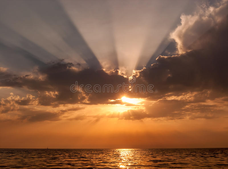 Beautiful scenic sunset seascape with sun peeping out from behind the cloud generating radiating sunrays and reflecting from water stock images