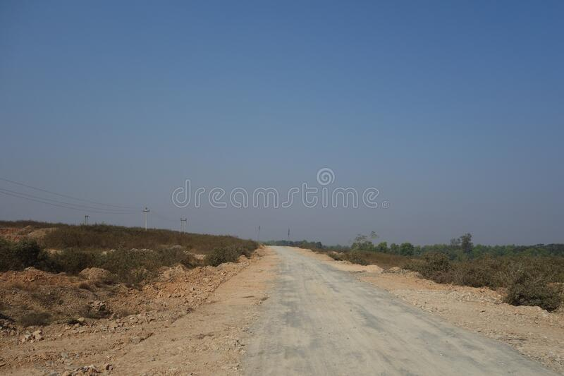 A beautiful scenic view of a Indian village road with blue sky as background stock photography